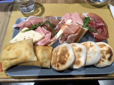 Tigella e gnocco fritto: due piatti tipici di Street Food della cucina romagnola rigorosamente accompagnati con salumi e formaggi